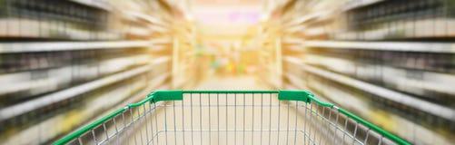 O carrinho de compras com garrafas de vinho arquiva no corredor do supermercado fotos de stock royalty free