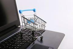 O carrinho de compras est? no port?til Conceito em linha das vendas imagem de stock