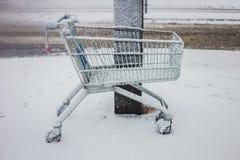 O carrinho de compras saiu na frente de um shopping, na neve fotos de stock