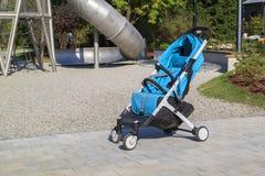 o carrinho de criança vazio está perto de um campo de jogos moderno com um grande meta foto de stock royalty free