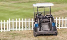 O carrinho de golfe estaciona perto da cerca de madeira branca em torno do cour do golfe Imagens de Stock