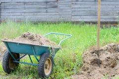 O carrinho de mão de duas rodas com terra localizou perto da pá na grama Foto de Stock Royalty Free