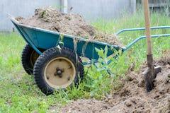 O carrinho de mão de duas rodas com terra localizou perto da pá na grama Fotos de Stock Royalty Free