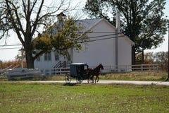 O carrinho passa a escola de Amish imagem de stock