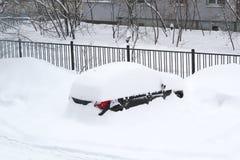 O carro é coberto quase completamente com a neve na jarda na frente da cerca fotografia de stock royalty free