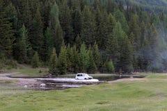 O carro é enviado através do rio Mönka da montanha perto da vila de Aktash no distrito de Ulagan da república de Altai fotos de stock