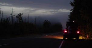 O carro é estacionado no lado da estrada na noite e perto do tronco do motorista video estoque