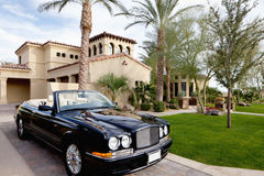 O carro aberto do telhado do preto estacionou a casa de mansão exterior Imagens de Stock