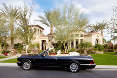 O carro aberto do telhado do preto estacionou na frente da casa de mansão Imagens de Stock