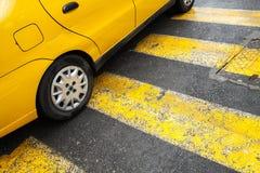 O carro amarelo do táxi está no cruzamento pedestre Fotografia de Stock Royalty Free