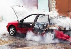 O carro ardente, lotes do fumo, fogo, procura um caminho mais curto fotos de stock