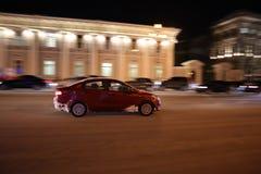 O carro atravessa rapidamente a cidade da noite foto de stock royalty free