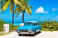 O carro azul americano de 1955 clássicos com um telhado branco estacionou direto na praia em Varadero Cuba imagem de stock royalty free