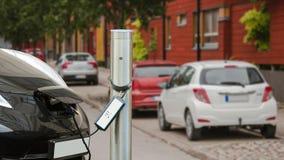 O carro bonde é carregado no parque de estacionamento perto da casa Os flashes de carregamento do indicador de processo filme