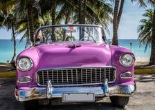 O carro clássico americano cor-de-rosa de HDR Cuba estacionou sob as palmas perto da praia em Varadero