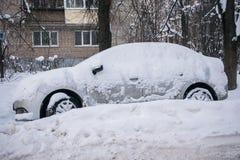 O carro, coberto com a camada grossa de neve, na jarda da casa residencial na cidade provilcial fotografia de stock
