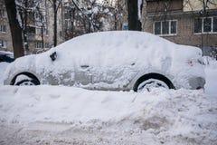 O carro, coberto com a camada grossa de neve, na jarda da casa residencial na cidade provilcial fotos de stock royalty free