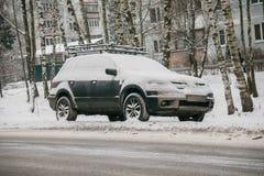 O carro, coberto com a camada grossa de neve, na jarda da casa residencial na cidade provilcial imagem de stock royalty free