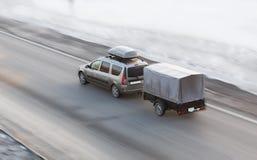 O carro com reboque monta na estrada do inverno Imagens de Stock Royalty Free