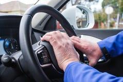 O carro da condução à direita, mão na roda buzina, o driver& x27; as mãos no tiro, cruise control de s abotoam-se na vista Foto de Stock