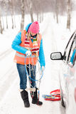 O carro da terra arrendada da mulher acorrenta a neve do pneu do inverno Imagens de Stock