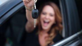 O carro da terra arrendada do excitador da mulher fecha a condução de seu carro novo vídeos de arquivo