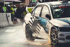 O carro da tração da evolução de Mitsubishi Lancer executa no asfalto molhado imagens de stock royalty free