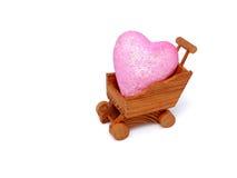 O carro de compra diminuto de madeira com coração isolou-se Fotos de Stock