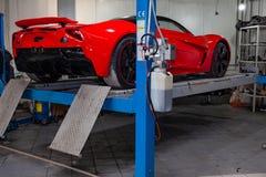 O carro de esportes vermelho aumentou em um elevador em uma oficina de reparações do carro, em um amortecedor traseiro e em uma d fotos de stock