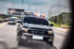 O carro de polícia zumbiu rapidamente para abrir a sirene, conduzindo ao longo de t fotos de stock