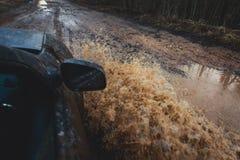 O carro de Suv 4wd monta através da poça enlameada, estrada fora de estrada da trilha, com um respingo grande, durante uma compet Imagens de Stock