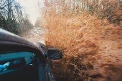 O carro de Suv 4wd monta através da poça enlameada, estrada fora de estrada da trilha, com um respingo grande, durante uma compet Imagem de Stock