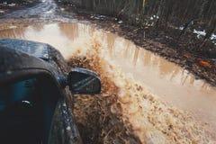 O carro de Suv 4wd monta através da poça enlameada, estrada fora de estrada da trilha, com um respingo grande, durante uma compet Foto de Stock Royalty Free