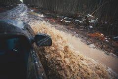 O carro de Suv 4wd monta através da poça enlameada, estrada fora de estrada da trilha, com um respingo grande, durante uma compet Imagem de Stock Royalty Free