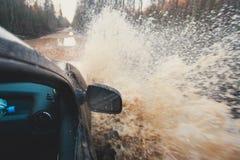 O carro de Suv 4wd monta através da poça enlameada, estrada fora de estrada da trilha, com um respingo grande, durante uma compet Fotografia de Stock Royalty Free
