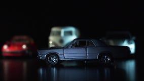 O carro do brinquedo é cinzento no primeiro plano, no fundo é uma frota de carros do brinquedo filme