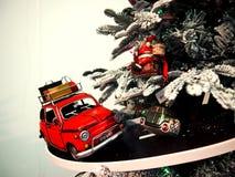 O carro do brinquedo monta na estrada em torno da árvore de Natal Fotografia de Stock Royalty Free