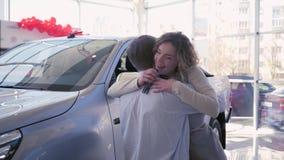 O carro do presente do dia das mulheres, indivíduo dá o veículo novo à menina de sorriso que os abraços felizes e mostram a chave video estoque