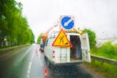 O carro do ` s dos trabalhadores da estrada através da janela com chuva deixa cair fotografia de stock