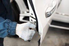 O carro do serralheiro reparará a porta de carro branca, foco seletivo à chave de fenda imagens de stock royalty free