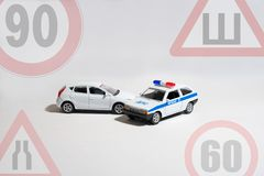 O carro e o carro de polícia em um fundo branco com os sinais das limitações fotos de stock