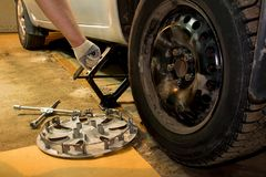 O carro em mudança do Mechanician roda dentro a garagem Homem que troca o pneu Servi?o do pneu imagens de stock