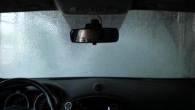 O carro em uma lavagem de carros automática Tiro da cabine No espelho são os olhos de um motorista da mulher 4K mo lento vídeos de arquivo