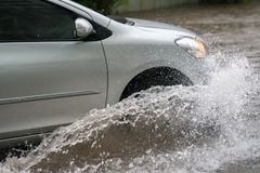 O carro espirra através de uma grande poça em uma rua inundada Imagem de Stock Royalty Free