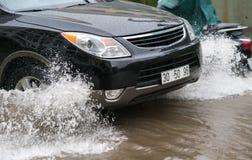O carro espirra através de uma grande poça em uma rua inundada Fotos de Stock