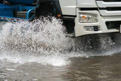O carro espirra através de uma grande poça em uma rua inundada Foto de Stock