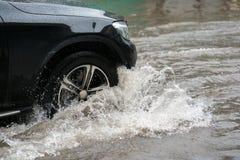 O carro espirra através de uma grande poça em uma rua inundada Imagem de Stock