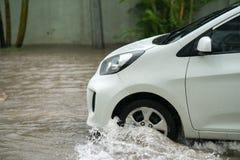 O carro espirra através de uma grande poça em uma rua inundada Fotografia de Stock