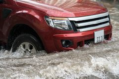 O carro espirra através de uma grande poça em uma rua inundada Imagens de Stock