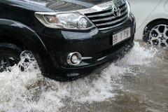 O carro espirra através de uma grande poça em uma rua inundada Fotos de Stock Royalty Free